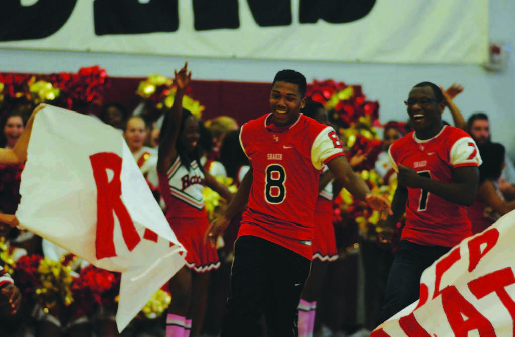 Senior Brian Jones runs through the Raider Nation banner at Homecoming Fest Oct. 11. Students and community members filled the bleachers while the Raiderettes, cheerleaders and band performed. The Fest was a success, with T-shirts, required for admission to the event, selling out days before, requiring a second order. Although the Fest was not formally called a pep rally, its characteristics embodied one.