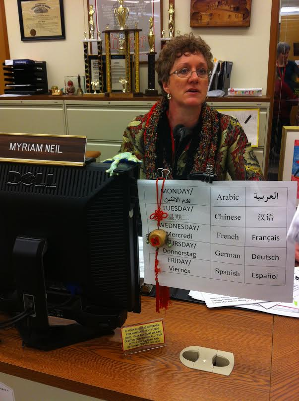 Administrative Assistant Myriam Neil's desk in the main office displays the schedule for the high school's language table. All students are welcome. The only requirement is that the designated language is spoken throughout the lunch period.