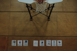 Posters demonstrating seven of the 10 learner profile attributes are taped to a gym wall beneath a basketball hoop.